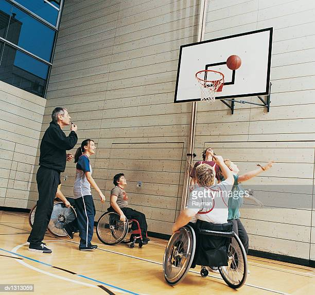 Teacher With Secondary School Students, Some in Wheelchairs, Playing Basketball