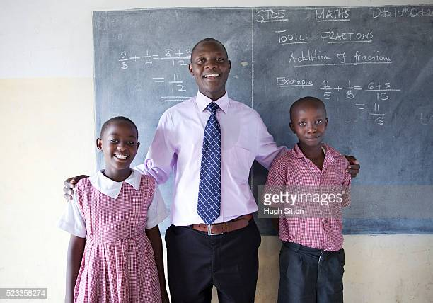 teacher with students (8-9) in primary school, maasai area, kenya - hugh sitton stock pictures, royalty-free photos & images