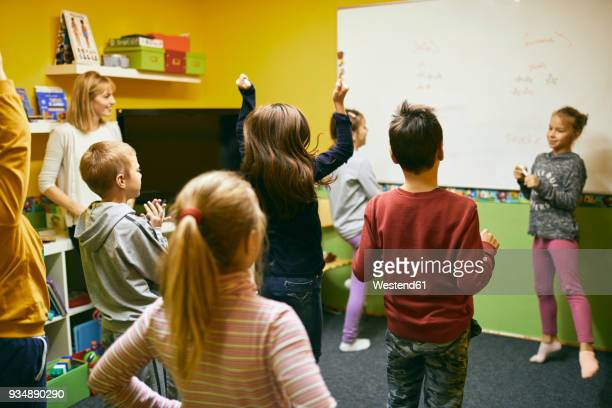 Teacher with students in relaxation room with whiteboard