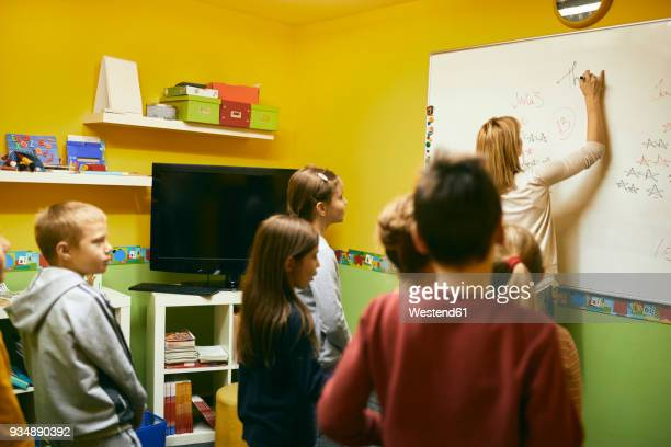 Teacher with students writing on whiteboard