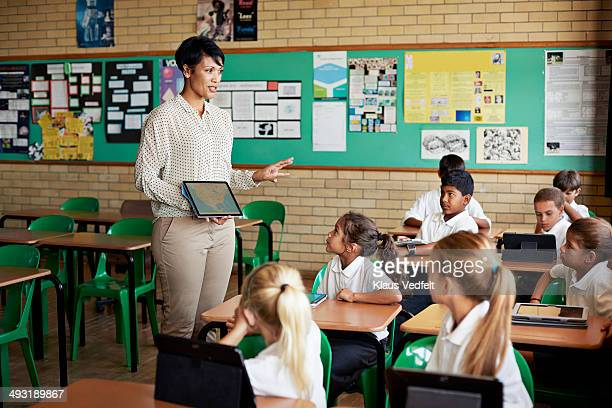 Teacher with tablet interacting with kids in class