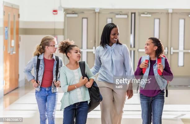 enseignant avec trois étudiants d'école primaire dans le couloir - enseignante photos et images de collection