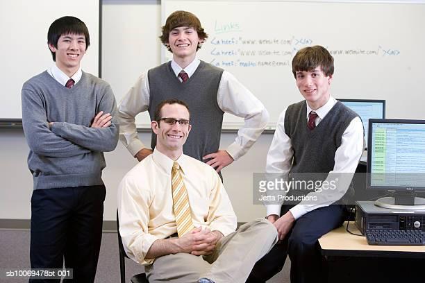 Enseignant avec trois garçons de l'école (de 16 à 18) en salle informatique, portrai