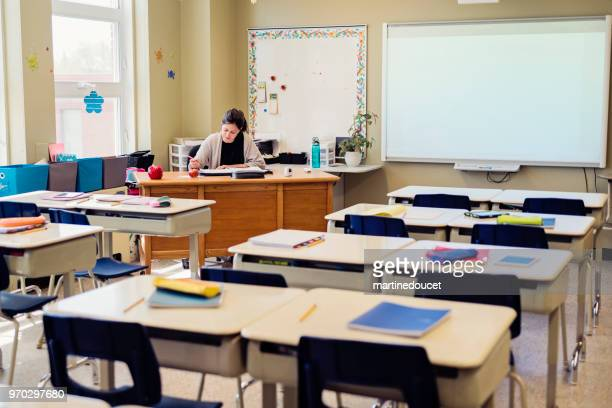 "teacher working at her desk in empty classroom. - ""martine doucet"" or martinedoucet stock pictures, royalty-free photos & images"