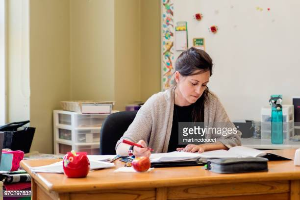 """teacher working at her desk in empty classroom. - """"martine doucet"""" or martinedoucet stock pictures, royalty-free photos & images"""