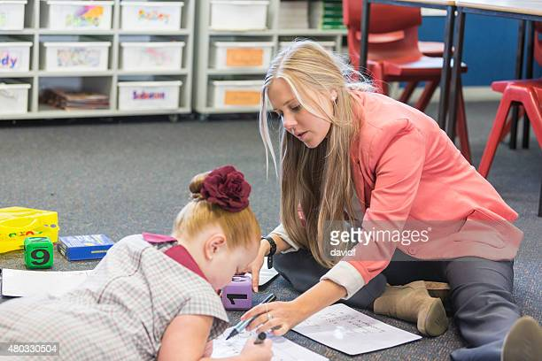 Teacher Working With a School Girl Sitting on the Floor