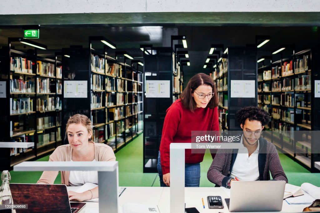 Teacher Working With her Students In Public Library : Stock Photo