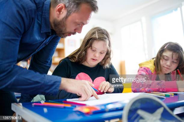 teacher working with special needs students at class - learning disability stock pictures, royalty-free photos & images
