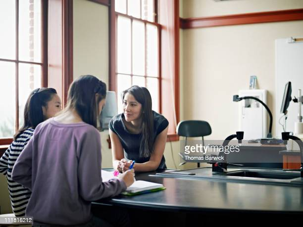Teacher working with two students in classroom