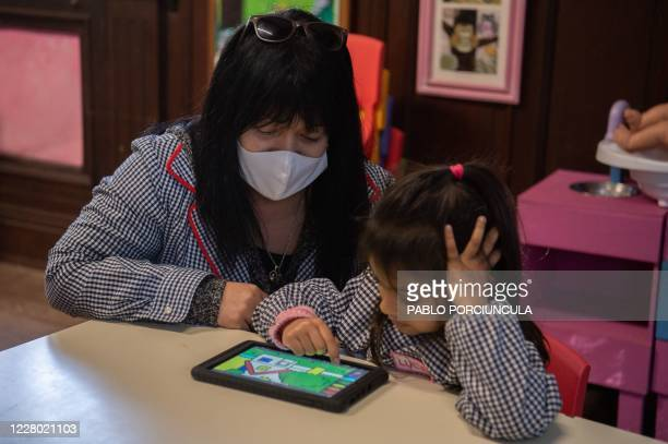 "Teacher works with a pre-school girl in her ""Ceibalita tablet"" during a class in a public school in Montevideo, amid the COVID-19 novel coronavirus..."