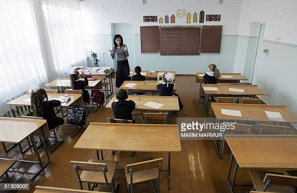 A teacher works with her class at school in Beslan North Ossetia 15 September 2004 as schools in the town reopen after the hostage crisis Students...
