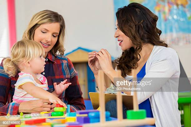 Teacher works with preschooler sitting on mother's lap