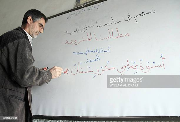 A teacher writes on a board 'We sit in our school until our demands are fulfilled the teachers of Sadr City want equity with those of Kurdistan'...