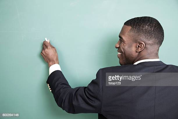 Teacher writes on chalkboard in high school classroom.