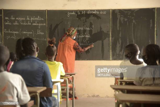 Teacher writes on the blackboard as students look during their first day back at school in Dakar on November 12, 2020. - After several months of...