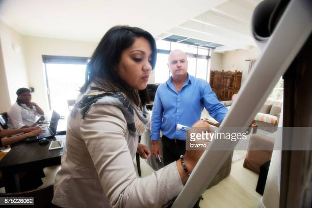 teacher writes on whiteboard with a marker pen - shareholder's meeting stock photos and pictures