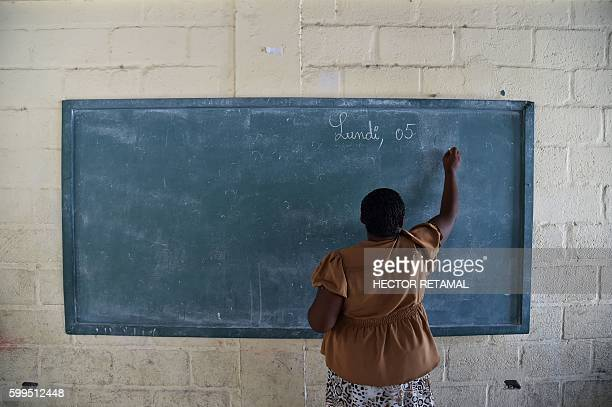 A teacher writes the date on a chalkboard on the first day back to school at the National School of Tabarre in the commune of Tabarre in the Haitian...