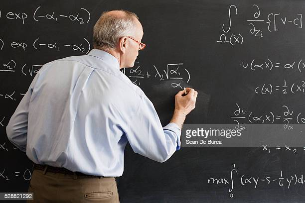 teacher writing algebra equation on chalkboard - professor stock pictures, royalty-free photos & images