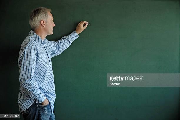 teacher writing at blackboard