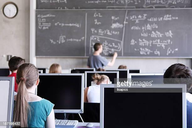 Lehrer auf Tafel Schreiben Formel auf überfüllten computer Zimmer.