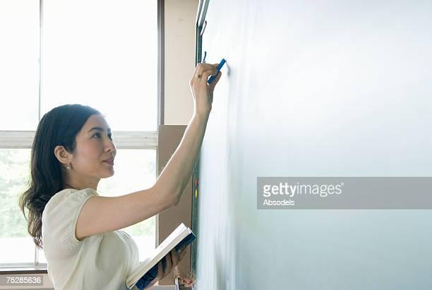 a teacher writing on a blackboard - enseignante photos et images de collection