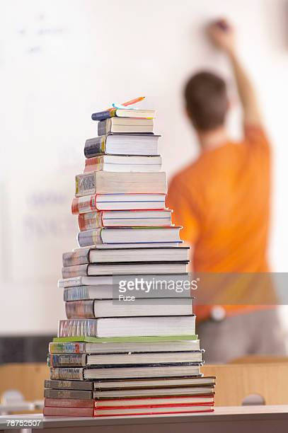 teacher writing on a whiteboard and a stack of books - mid adult men fotografías e imágenes de stock