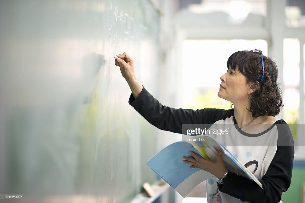 Teacher writing on chalkboard : Stock Photo