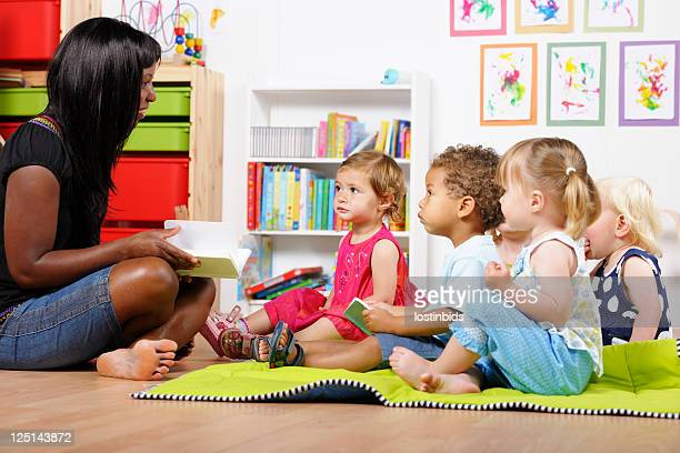 teacher/carer/ childminder reading to a group of toddlers at nursery - toddler stock pictures, royalty-free photos & images