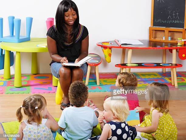 teacher/carer/ childminder reading to a group of toddlers - black nativity stock photos and pictures