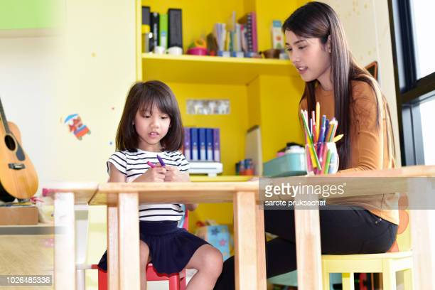 teachers and child having fun on learning  in an international school .teacher ,education, kid and primary school concept . - ammunition magazine stock photos and pictures