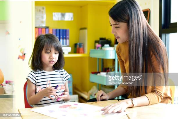 teachers and child having fun on learning  in an international school . - ammunition magazine stock photos and pictures