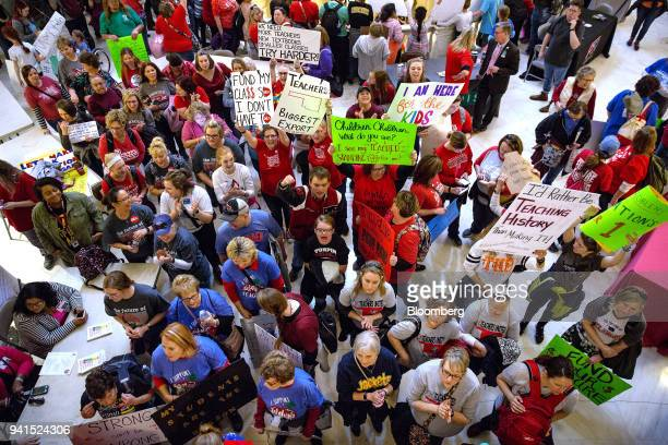 Teachers and demonstrators hold signs during a rally inside the Oklahoma State Capitol building in Oklahoma City Oklahoma US on Tuesday April 3 2018...