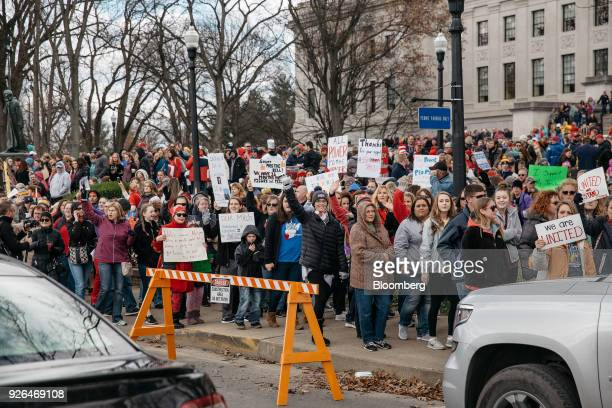 Teachers and demonstrators hold signs during a rally outside the West Virginia Capitol in Charleston, West Virginia, U.S., on Friday, March 2, 2018....