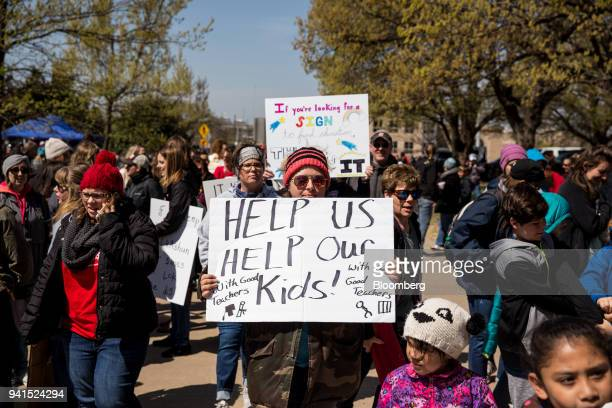 Teachers and demonstrators hold signs during a strike outside the Oklahoma State Capitol building in Oklahoma City Oklahoma US on Tuesday April 3...