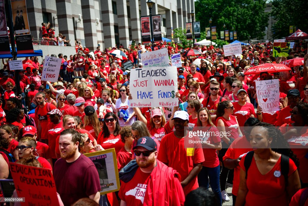 Teachers and supporters hold signs during a 'March For Students And Rally For Respect' protest in Raleigh, North Carolina, U.S., on Wednesday, May 16, 2018. At least 29 North Carolina public school districts serving 865,000 students will close their doors asteachers walk out in the fifth large-scale demonstration in less than three months in states with Republican-led legislatures, most of them organized on the internet in places where unions are weak. Photographer: Charles Mostoller/Bloomberg via Getty Images
