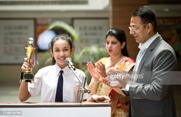 teachers applauding for student at awards ceremony - indian ethnicity stock pictures, royalty-free photos & images
