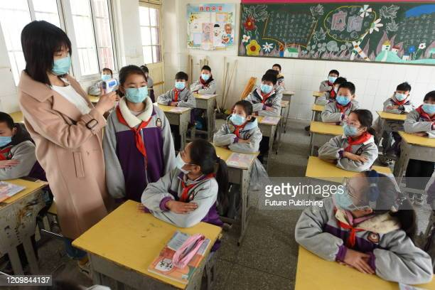 Teachers are guiding students to wear masks correctly, Donghai County, Jiangsu Province, China, April 14, 2020.- PHOTOGRAPH BY Costfoto / Barcroft...