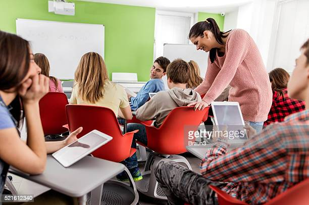 Teacher's assistance in using digital tablet in the classroom.