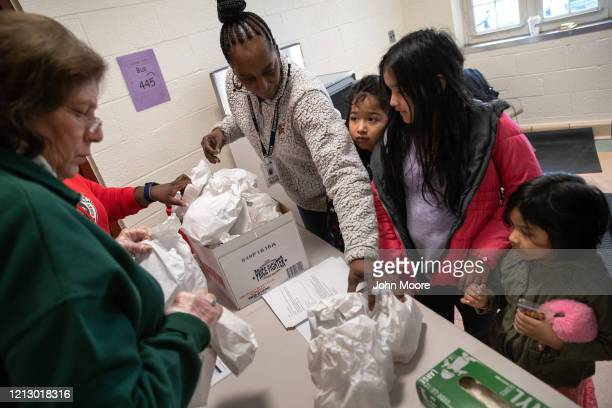 Teachers at KT Murphy Elementary School give out bagged meals to children as part of Stamford Public Schools' Grab and Go Meals for Kids program...