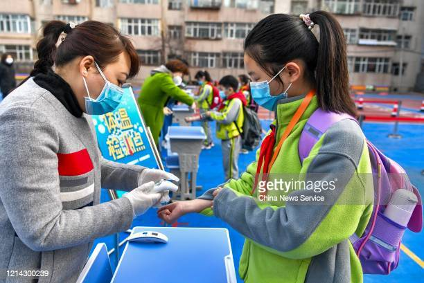 Teachers check the body temperature of students at No42 primary school amid the coronavirus outbreak on March 23 2020 in Urumqi Xinjiang Uygur...