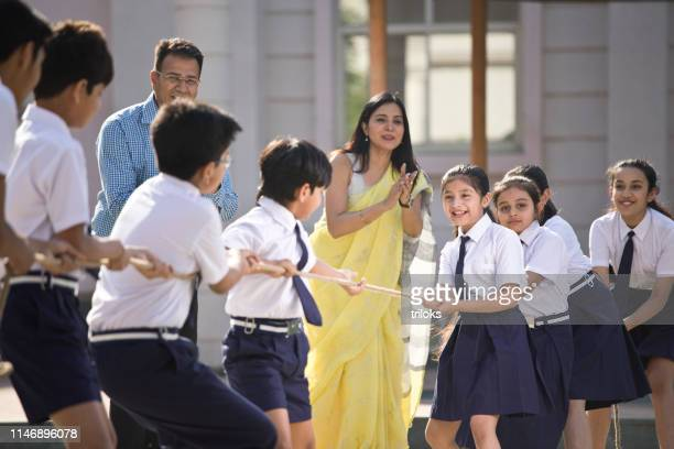 teachers cheering student playing tug of war - asian boy stock pictures, royalty-free photos & images