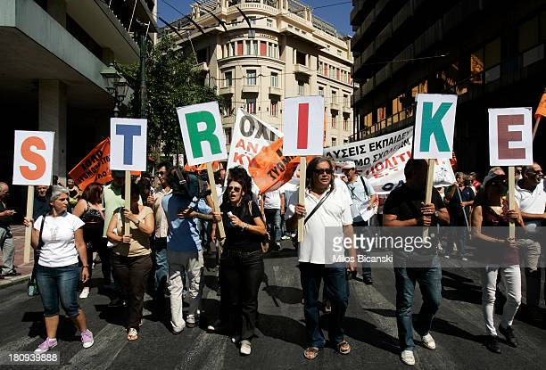 Teachers hold a banner reading 'strike' during protests against austerity and job cuts on September 18 2013 in Athens Greece As part of the...