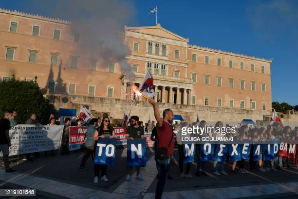 """Teachers hold letters forming the phrase """"This bill won't pass"""" in front of the Greek Parliament in Athens on June 10 during a protest against the..."""