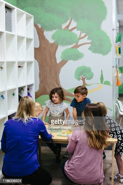 teachers kneeling at a table with children gathered around - calabasas stock pictures, royalty-free photos & images