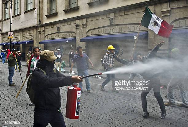 Teachers protesting against an education reform clash with the Mexican Federal Police at Mexico City's Zocalo square on September 13 2013 Antiriot...