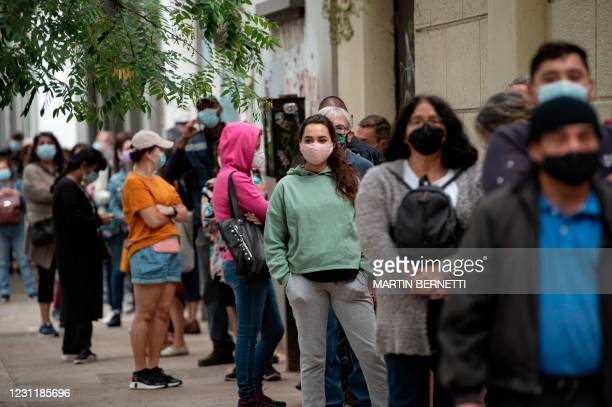 Teachers queue at a vaccination centre in Santiago, on February 15 to receive a dose of the Chinese-made COVID-19 vaccine CoronaVac amid the novel...