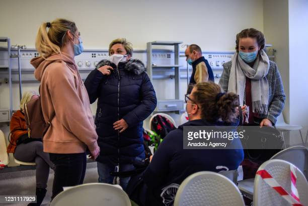 Teachers wear protective face masks as they wait to be given an Oxford-AstraZeneca coronavirus jab at the Krakow University Hospital in Krakow,...
