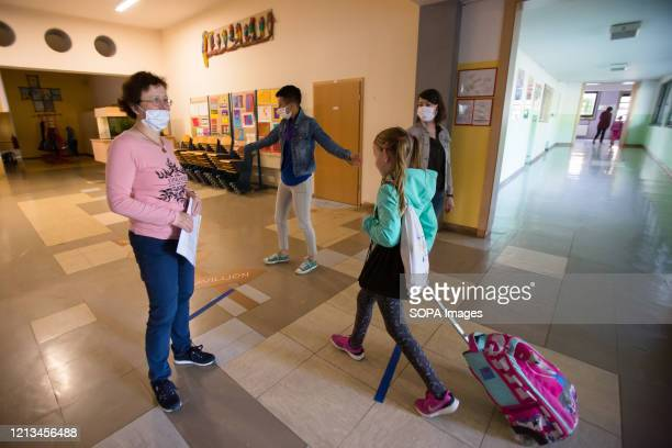 Teachers wearing face masks as preventive measure guide children to their classes as they return to school under strict safety measures. Pupils of...