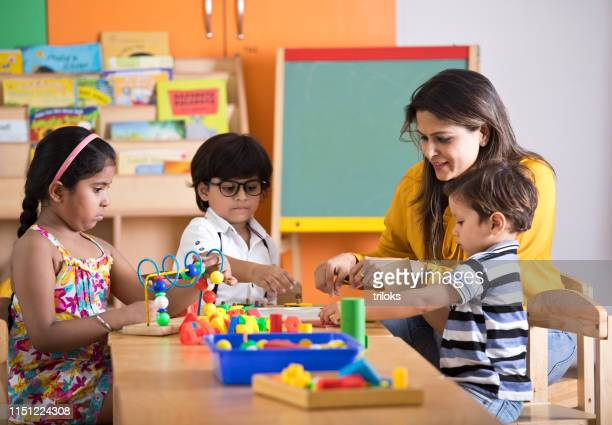 teachers with children learning at preschool - indian ethnicity stock pictures, royalty-free photos & images