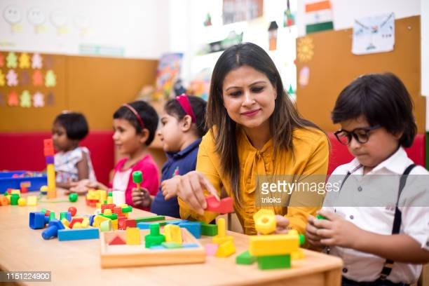 teachers with children learning at preschool - leisure facilities stock pictures, royalty-free photos & images